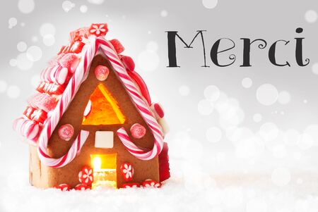 french text: Gingerbread House In Snowy Scenery As Christmas Decoration. Candlelight For Romantic Atmosphere. Silver Background With Bokeh Effect. French Text Merci Means Thank You
