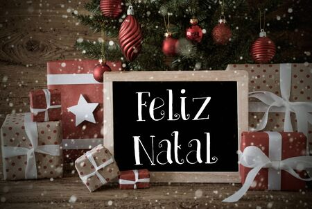 nostalgic: Nostalgic Christmas Card For Seasons Greetings. Christmas Tree With Balls And Snowflakes. Gifts In The Front Of Wooden Background. Chalkboard With Portuguese Text Feliz Natal Means Merry Christmas