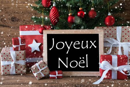 french text: Colorful Christmas Card For Seasons Greetings. Christmas Tree With Balls And Snowflakes. Gifts In Front Of Wooden Background. Chalkboard With French Text Joyeux Noel Means Merry Christmas