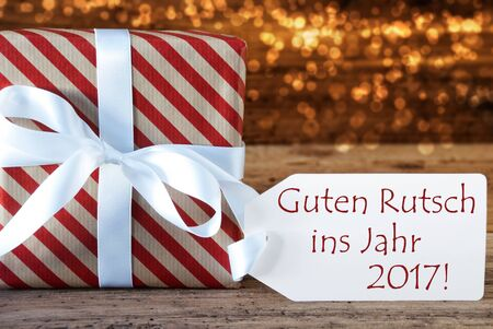ins: Macro Of Christmas Gift Or Present On Atmospheric Wooden Background. Card For Seasons Greetings Or Congratulations. White Ribbon With Bow. German Text Guten Rutsch Ins Jahr 2017 Means Happy New Year
