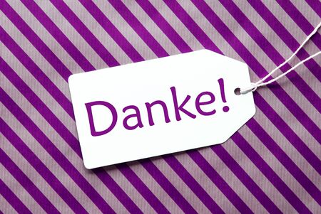 thankfulness: One Label On A Purple Striped Wrapping Paper. Textured Background. Tag With Ribbon. German Text Danke Means Thank You