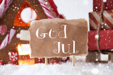 house of god: Gingerbread House In Snowy Scenery As Christmas Decoration. Sleigh With Christmas Gifts Or Presents And Snowflakes. Label With Swedish Text God Jul Means Merry Christmas Stock Photo