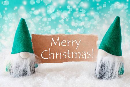 turqoise: Christmas Greeting Card With Two Turqoise Gnomes. Sparkling Bokeh Background With Snow. English Text Merry Christmas