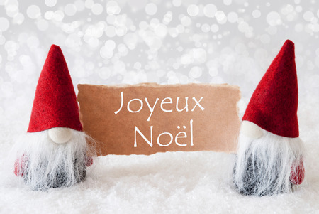 french text: Christmas Greeting Card With Two Red Gnomes. Sparkling Bokeh Background With Snow. French Text Joyeux Noel Means Merry Christmas