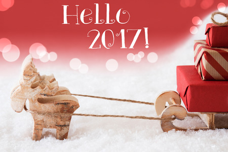 christmassy: Moose Is Drawing A Sled With Red Gifts Or Presents In Snow. Christmas Card For Seasons Greetings. Red Christmassy Background With Bokeh Effect. English Text Hello 2017 For Happy New Year