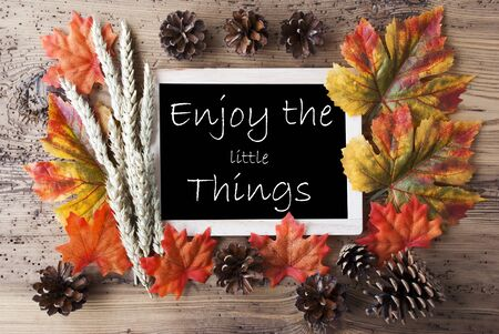 Blackboard With Autumn Or Fall Decoration. Greeting Card For Seasons Greetings. Colorful Leaves, Fir Cone And Barley On Aged Wooden Background. English Quote Enjoy The Little Things