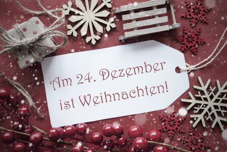 ist: Nostalgic Christmas Decoration Like Gift Or Present, Sleigh. Card For Seasons Greetings With Red Paper Background. German Text Am 24. Dezember Ist Weihnachten Means Christmas
