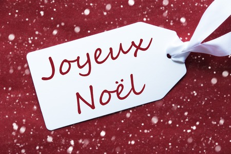 french text: One White Label On A Red Textured Background. Tag With Ribbon And Snowflakes. French Text Joyeux Noel Means Merry Christmas