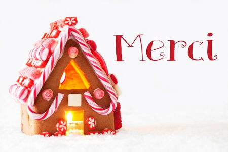 french text: Gingerbread House In Snowy Scenery As Christmas Decoration With White Background. Candlelight For Romantic Atmosphere. French Text Merci Means Thank You Stock Photo