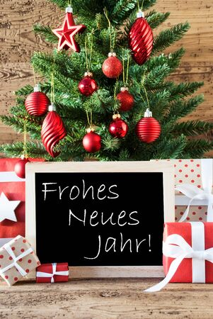 christmas tree presents: Colorful Christmas Card For Seasons Greetings. Christmas Tree With Balls. Gifts Or Presents In The Front Of Wooden Background. Chalkboard With German Text Frohes Neues Jahr Means Happy New Year