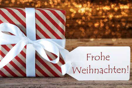 atmospheric: Macro Of Christmas Gift Or Present On Atmospheric Wooden Background. Card For Seasons Greetings Or Congratulations. White Ribbon With Bow. German Text Frohe Weihnachten Means Merry Christmas