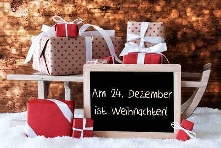 weihnachten: Chalkboard With German Text Am 24. Dezember Ist Weihnachten Means December 24th Is Christmas Eve. Sled With Christmas And Winter Decoration. Presents On Snow With Wooden Background And Bokeh Effect. Stock Photo