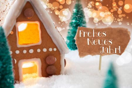jahr: Gingerbread House In Snowy Scenery As Christmas Decoration. Christmas Trees And Candlelight. Bronze And Orange Background With Bokeh Effect. German Text Frohes Neues Jahr Means Happy New Year Stock Photo