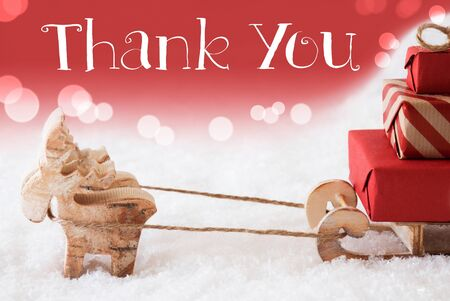 christmassy: Moose Is Drawing A Sled With Red Gifts Or Presents In Snow. Christmas Card For Seasons Greetings. Red Christmassy Background With Bokeh Effect. English Text Thank You Stock Photo