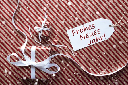 jahr: Two Gifts Or Presents With White Ribbon. Red And Brown Striped Wrapping Paper. Christmas Or Greeting Card With Snowflakes. Label With German Text Frohes Neues Jahr Means Happy New Year Stock Photo