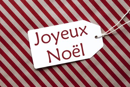joyeux: One Label On A Red And Brown Striped Wrapping Paper. Textured Background. Tag With Ribbon. French Text Joyeux Noel Means Merry Christmas Stock Photo