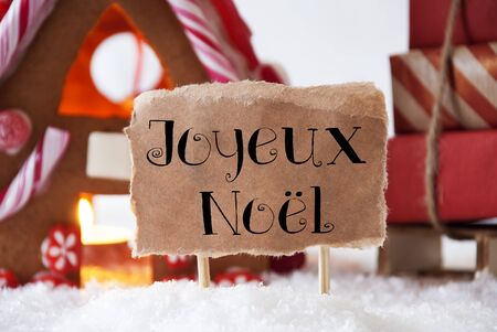french text: Gingerbread House In Snowy Scenery As Christmas Decoration. Sleigh With Christmas Gifts Or Presents. Label With French Text Joyeux Noel Means Merry Christmas