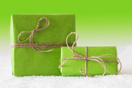 birthday presents: Two Green Christmas Presents On Snow. Card For Birthday Or Seasons Greetings. Natural looking Ribbon. Green Background