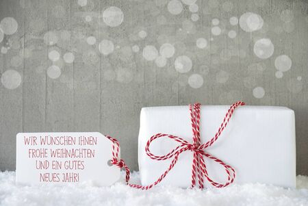 frohe: One Christmas Gift Or Present On Snow. Cement Wall As Background With Bokeh. Modern And Urban Style. Label With German Text Frohe Weihnachten Und Ein Gutes Neues Jahr Means Merry Christmas And Happy New Year