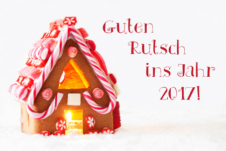 ins: Gingerbread House In Snowy Scenery As Christmas Decoration With White Background. Candlelight For Romantic Atmosphere. German Text Guten Rutsch Ins Jahr 2017 Means Happy New Year