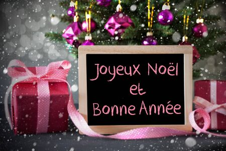 bonne: Chalkboard With French Text Joyeux Noel Et Bonne Annee Means Merry Christmas And Happy New Year. Christmas Tree With Rose Quartz Balls, Snowflakes And Bokeh Effect.Gifts In Front Of Cement Background. Stock Photo