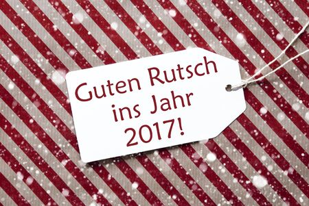 ins: One Label On A Red And Brown Striped Wrapping Paper. Textured Background With Snowflakes. Tag With Ribbon. English Text Guten Rutsch Ins Jahr 2017 Means Happy New Year