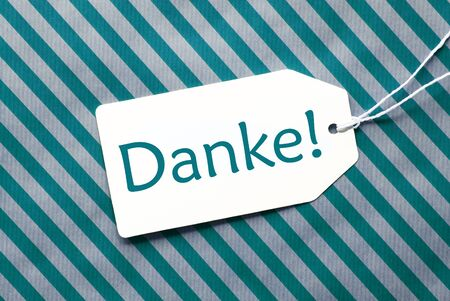 thankfulness: One Label On A Turquoise Striped Wrapping Paper. Textured Background. Tag With Ribbon. German Text Danke Means Thank You Stock Photo