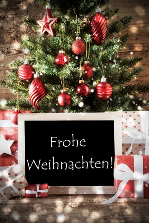 weihnachten: Christmas Tree With Balls And Snowflakes. Gifts Or Presents In The Front Of Wooden Background With Bokeh Effect. Chalkboard With German Text Frohe Weihnachten Means Merry Christmas