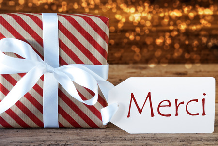 atmospheric: Macro Of Christmas Gift Or Present On Atmospheric Wooden Background. Card For Seasons Greetings, Best Wishes Or Congratulations. White Ribbon With Bow. French Text Merci Means Thank You Stock Photo