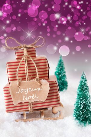 joyeux: Vertical Image Of Sleigh Or Sled With Christmas Gifts Or Presents. Snowy Scenery With Snow And Trees. Purple Sparkling Background With Bokeh. Label With French Text Joyeux Noel Means Merry Christmas