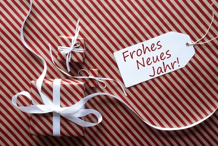 jahr: Two Gifts Or Presents With White Ribbon. Red And Brown Striped Wrapping Paper. Christmas Or Greeting Card. Label With German Text Frohes Neues Jahr Means Happy New Year