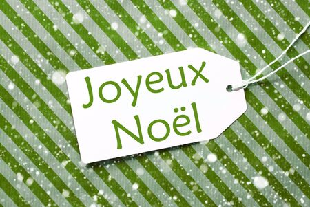 joyeux: One Label On A Green Striped Wrapping Paper. Textured Background With Snowflakes. Tag With Ribbon. French Text Joyeux Noel Means Merry Christmas