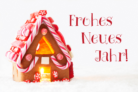 Gingerbread House In Snowy Scenery As Christmas Decoration With White Background. Candlelight For Romantic Atmosphere. German Text Frohes Neues Jahr Means Happy New Year Stock Photo