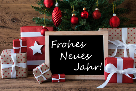christmas tree presents: Colorful Christmas Card For Seasons Greetings. Christmas Tree With Red Balls. Gifts Or Presents In The Front Of Wooden Background. Chalkboard With German Text Frohes Neues Jahr Means Happy New Year