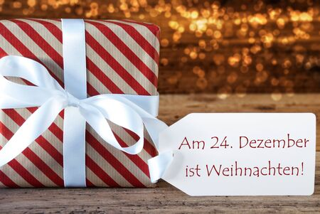 atmospheric: Macro Of Christmas Gift Or Present On Atmospheric Wooden Background. Card For Seasons Greetings, Best Wishes Or Congratulations. White Ribbon With Bow. German Text Weihnachten Means Christmas Stock Photo