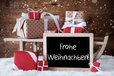 frohe: Chalkboard With German Text Frohe Weihnachten Means Merry Christmas. Sled With Christmas And Winter Decoration And Snowflakes. Gifts And Presents On Snow With Wooden Background.
