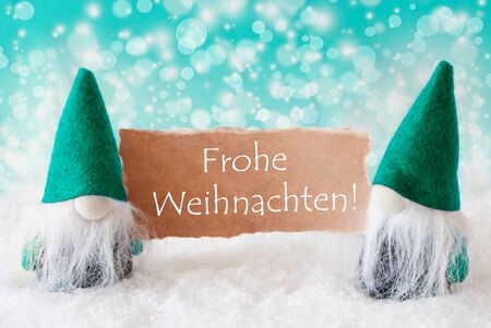 turqoise: Christmas Greeting Card With Two Turqoise Gnomes. Sparkling Bokeh Background With Snow. German Text Frohe Weihnachten Means Merry Christmas Stock Photo