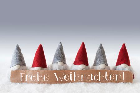 gnomos: Etiqueta con el texto alem�n Frohe Weihnachten significa Feliz Navidad. Tarjeta de felicitaci�n de Navidad con gnomos. Antecedentes de plata con nieve. Foto de archivo