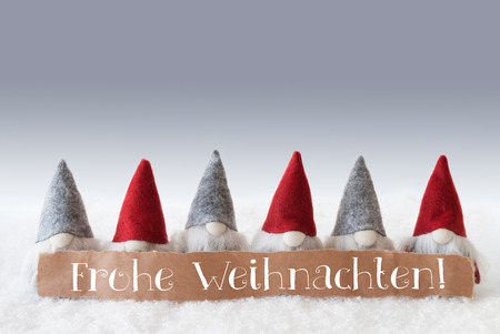 Label With German Text Frohe Weihnachten Means Merry Christmas. Christmas Greeting Card With Gnomes. Silver Background With Snow.