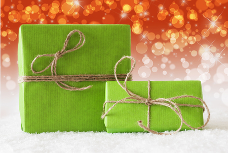 complementary: Two Green Christmas Gift Or Present On Snow. Card For Birthday Or Seasons Greetings. Natural looking Ribbon. Background With Complementary Red Orange Bokeh Effect Stock Photo