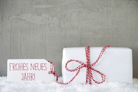 jahr: One Christmas Gift Or Present On Snow. Cement Or Concrete Wall As Background. Modern And Urban Style. Card For Birthday Greetings. Label With German Text Frohes Neues Jahr Means Happy New Year Stock Photo
