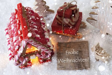 weihnachten: Label With German Text Frohe Weihnachten Means Merry Christmas. Gingerbread House On Snow With Christmas Decoration Like Trees And Moose. Sleigh With Christmas Gifts Or Presents And Snowflakes. Stock Photo