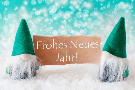 jahr: Christmas Greeting Card With Two Turqoise Gnomes. Sparkling Bokeh Background With Snow. German Text Frohes Neues Jahr Means Happy New Year