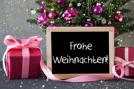 frohe: Chalkboard With German Text Frohe Weihnachten Means Merry Christmas. Christmas Tree With Rose Quartz Balls, Snowflakes. Gifts Or Presents In The Front Of Cement Background. Stock Photo