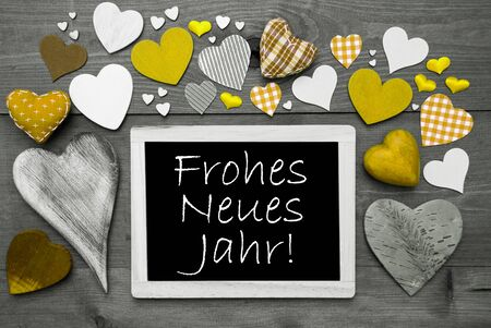 jahr: Chalkboard With German Text Frohes Neues Jahr Means Happy New Year. Many Yellow Textile Hearts. Grey Wooden Background With Vintage, Rustic Or Retro Style. Black And White Style With Colored Hot Spots
