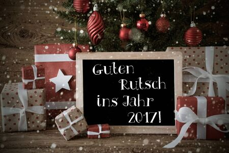jahr: Nostalgic Card For Seasons Greetings. Christmas Tree With Balls And Snowflakes. Gifts In The Front Of Wooden Background. Chalkboard With German Text Guten Rutsch Ins Jahr 2017 Means Happy New Year