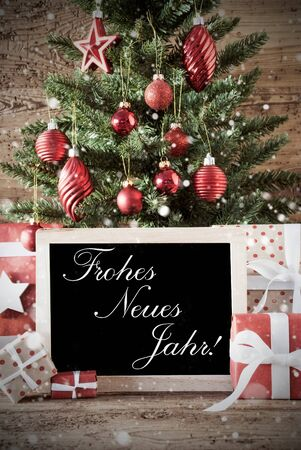 jahr: Nostalgic Christmas Card For Seasons Greetings. Christmas Tree With Balls. Gifts Or Presents In The Front Of Wooden Background. Chalkboard With German Text Frohes Neues Jahr Means Happy New Year