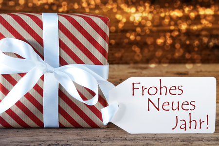 Macro Of Christmas Gift Or Present On Atmospheric Wooden Background. Card For Seasons Greetings Or Congratulations. White Ribbon With Bow. German Text Frohes Neues Jahr Means Happy New Year