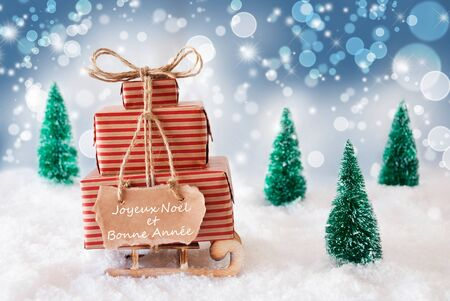 bonne: Sleigh Or Sled With Christmas Gifts Or Presents On Snow. Blue Sparkling Background With Bokeh Effect. Label With French Text Joyeux Noel Et Bonne Annee Means Merry Christmas And Happy New Year