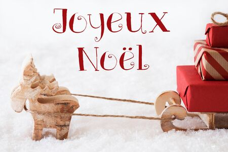 joyeux: Moose Is Drawing A Sled With Red Gifts Or Presents In Snow. Christmas Card For Seasons Greetings. French Text Joyeux Noel Means Merry Christmas Stock Photo